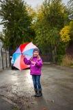 Niña pequeña linda divertida que lleva la capa impermeable con el paraguas colorido fotos de archivo