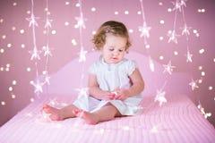 Niña pequeña linda en una cama blanca entre las luces rosadas Fotos de archivo