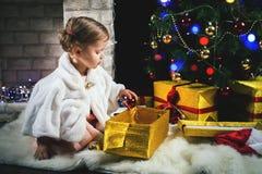 Niña pequeña linda que adorna un árbol de navidad Imágenes de archivo libres de regalías