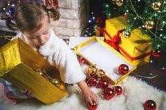 Niña pequeña linda que adorna un árbol de navidad Bolas rojas Imagen de archivo