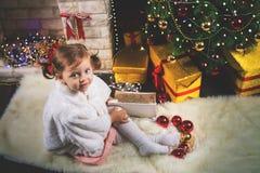 Niña pequeña linda que adorna un árbol de navidad Bolas rojas Fotos de archivo libres de regalías