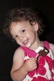 Niña pequeña linda que come el helado fotografía de archivo