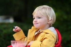 Niña pequeña linda que come el helado al aire libre en café Imagen de archivo libre de regalías