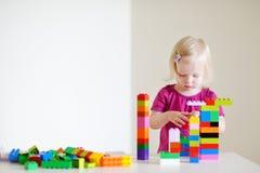 Niña pequeña linda que juega con los bloques coloridos Fotos de archivo