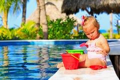 Niña pequeña linda que juega en piscina en Fotos de archivo libres de regalías