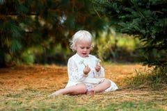 Niña pequeña linda que se sienta afuera debajo de los árboles que exploran la naturaleza foto de archivo libre de regalías