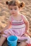 Niña pequeña morena de los ojos azules que juega con la arena en playa Fotografía de archivo