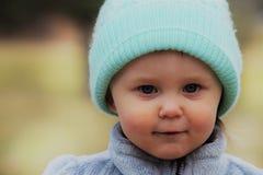 Niña pequeña observada azul grining Imagenes de archivo