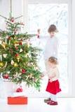 Niña pequeña que ayuda a su hermano a adornar el árbol de navidad Fotos de archivo libres de regalías