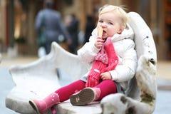 Niña pequeña que come el helado al aire libre en el invierno Foto de archivo