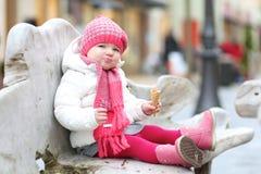 Niña pequeña que come el helado al aire libre en el invierno Imagenes de archivo
