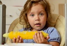 Niña pequeña que come maíz Imágenes de archivo libres de regalías