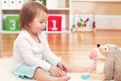 Niña pequeña que juega con sus peluches Foto de archivo libre de regalías