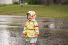 Niña pequeña que juega en la lluvia Fotos de archivo