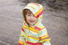 Niña pequeña que juega en la lluvia Imagenes de archivo