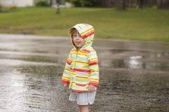 Niña pequeña que juega en la lluvia Imágenes de archivo libres de regalías