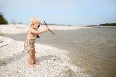 Niña pequeña que juega en los palillos que lanzan de la playa en el agua imágenes de archivo libres de regalías