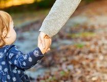 Niña pequeña que lleva a cabo las manos con su madre en un día de la caída Fotografía de archivo libre de regalías