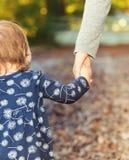 Niña pequeña que lleva a cabo las manos con su madre en un día de la caída Fotos de archivo libres de regalías