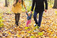 Niña pequeña que lleva a cabo las manos con su madre y padre afuera en un día de la caída Fotos de archivo