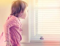 Niña pequeña que mira a escondidas de la ventana imagen de archivo libre de regalías