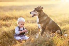 Niña pequeña que se sienta afuera en la oscuridad con el perro casero Imagen de archivo