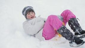 Niña pequeña que va abajo de un trineo en una colina nevosa metrajes