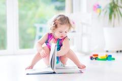 Niña pequeña rizada divertida en libro de lectura rosado del vestido fotos de archivo libres de regalías