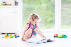 Niña pequeña rizada divertida que lee un libro que se sienta en piso fotos de archivo