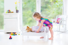 Niña pequeña rizada dulce que juega con su oso de peluche Imágenes de archivo libres de regalías