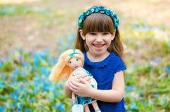 Niña pequeña sonriente con una muñeca en sus manos Foto de archivo