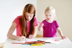 Niña pequeña y su dibujo de la mamá con los lápices Imágenes de archivo libres de regalías