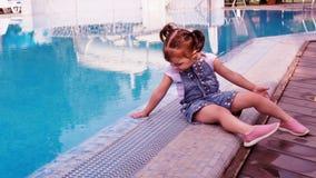 Niña por la piscina azul Un pequeño niño está jugando por la piscina Una niña hermosa se está sentando al borde de a almacen de metraje de vídeo