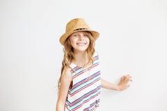 Niña preciosa con el sombrero de paja contra un fondo blanco Foto de archivo