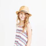 Niña preciosa con el sombrero de paja contra un fondo blanco Foto de archivo libre de regalías