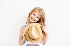 Niña preciosa con el sombrero de paja contra un fondo blanco Fotografía de archivo