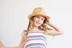 Niña preciosa con el sombrero de paja contra un fondo blanco Ha Fotos de archivo