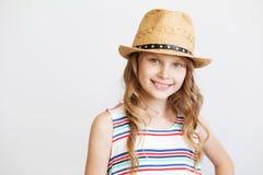 Niña preciosa con el sombrero de paja en el fondo blanco Imagenes de archivo