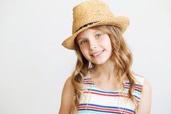 Niña preciosa con el sombrero de paja en un fondo blanco Imagen de archivo libre de regalías