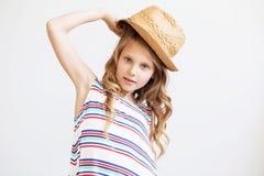 Niña preciosa con el sombrero de paja en un fondo blanco Fotografía de archivo libre de regalías