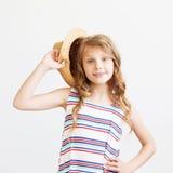 Niña preciosa con el sombrero de paja y el vestido rayado contra un fondo blanco Fotografía de archivo libre de regalías