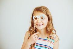 Niña preciosa con los vidrios divertidos de la forma del corazón del papel del partido o Foto de archivo libre de regalías
