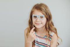 Niña preciosa con los vidrios divertidos de la forma del corazón del papel del partido o Fotos de archivo libres de regalías