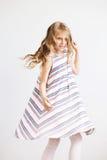 Niña preciosa en un vestido rayado contra un fondo blanco Imagen de archivo libre de regalías
