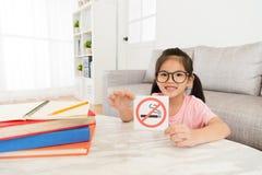 Niña preciosa que presenta el aviso de no fumadores imagen de archivo