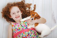 Niña que abraza con su amigo del perrito Foto de archivo