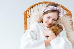 Niña que abraza el conejo peludo lindo aislado en blanco Imagen de archivo libre de regalías