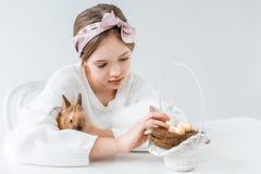 Niña que abraza el conejo y que mira la cesta con los huevos de Pascua en jerarquía Imágenes de archivo libres de regalías