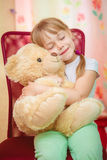 Niña que abraza el oso de peluche Fotos de archivo