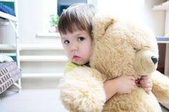 Niña que abraza el oso de peluche interior, dedicación concentrada imagen de archivo